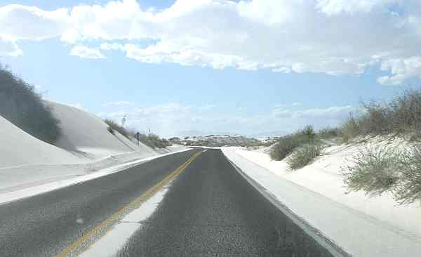 Sand covered road leading through White Sands National Monument.