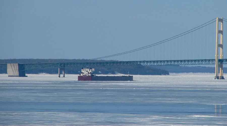 Freighter passing under the Mackinac Bridge in winter.