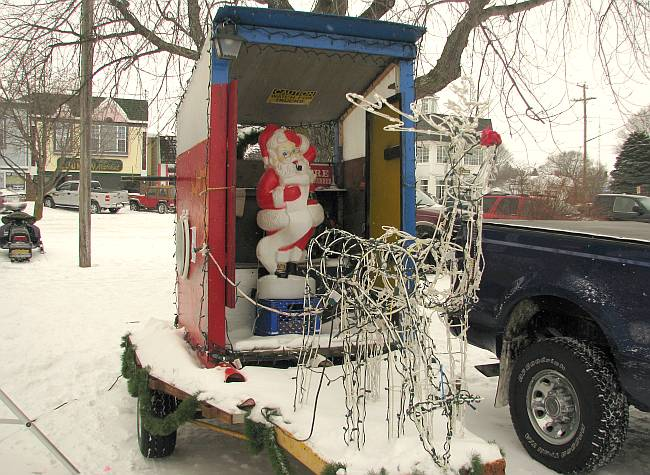 Santa Claus in an outhouse pulled by reindeer.