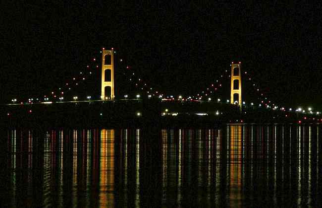 Mackinac Bridge at night with lights reflecting off the water